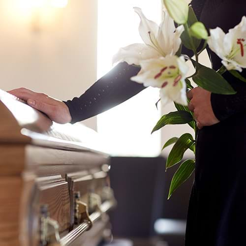 A wood casket and a woman holding white lillies with her hand on the casket