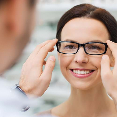 Woman trying on glasses with her eye doctor