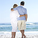 A couple at retirement age standing on a beach